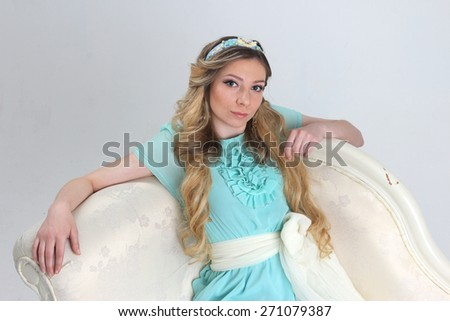 Pretty young woman dreaming leaned back on white sofa - stock photo