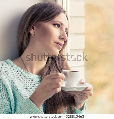 Pretty young woman drinking espresso sitting on the window sill. Dreamy european girl enjoying with cup of coffee looking through window - stock photo