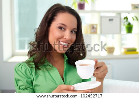 Pretty young woman drinking tea and looking at camera - stock photo