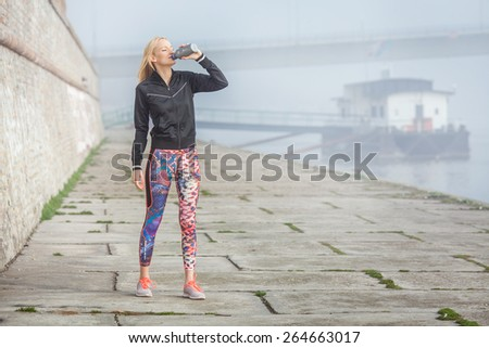 Pretty young woman drinking water while taking a break after jogging - stock photo