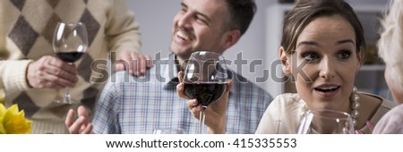 Pretty young woman drinking wine and talking with her mother on family dinner. Behind her husband talking with father-in-law - stock photo