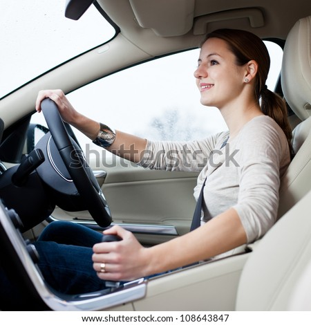 Pretty young woman driving her brand new car shallow DOF; color toned image) - stock photo