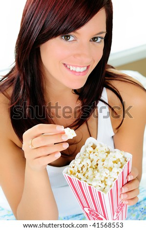 Pretty Young Woman Eating Popcorn While  Watching A Movie In Bed - stock photo