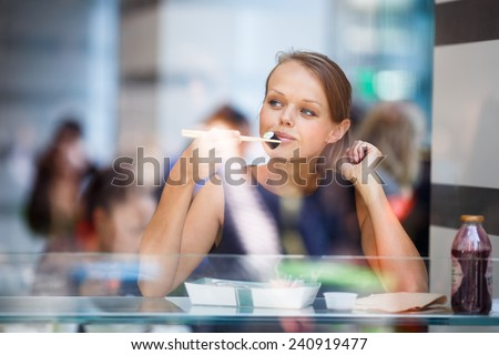 Pretty, young woman eating sushi in a restaurant, having her lunch break, enjoying the food, pausing for a while from her busy corporate/office life (color toned image) - stock photo