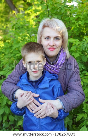 pretty young woman embracing her little son in the park - stock photo