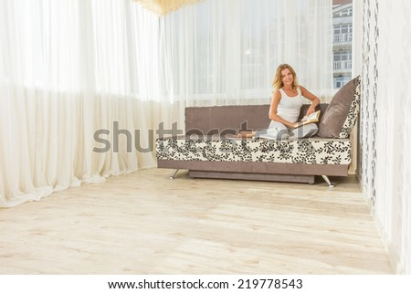 Pretty young woman enjoying reading a book at home. - stock photo
