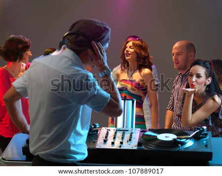 pretty young woman flirting with the dj in a night club - stock photo
