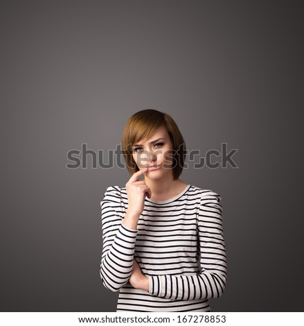 Pretty young woman gesturing with empty space - stock photo