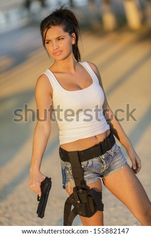 Pretty young woman holding a gun on a sunny day - stock photo