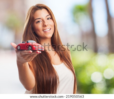 pretty young woman holding a red car toy - stock photo