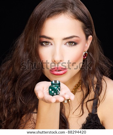 pretty young woman holding dices on black background - stock photo