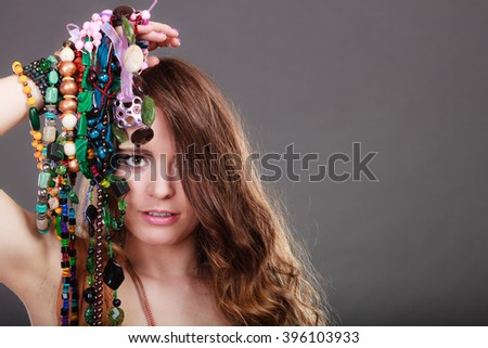 Pretty young woman holding many plentiful of precious jewelry necklaces beads. Portrait of gorgeous fashion girl in studio on gray. - stock photo