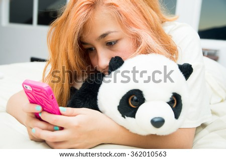 Pretty young woman horizontally lying cozy in bed using pink mobile phone and stuffed panda animal. - stock photo