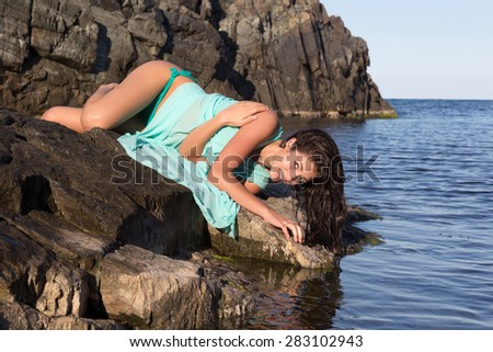 Pretty young woman in a green chiffon dress on a beach rock - stock photo