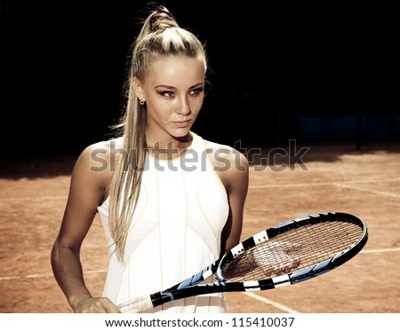 Pretty young woman in a tennis dress and with the racket in her hand standing on a sandy court - stock photo