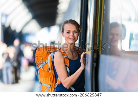 Pretty, young woman in a train station, waiting for her train, boarding a train (color toned image) - stock photo
