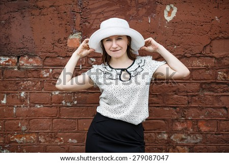 Pretty young woman in a white blouse and hat posing on a background old vintage brown brick wall. Female holds the edges of the hat by hand. Photo in retro style. - stock photo