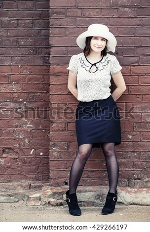 Pretty young woman in a white hat, blouse and black skirt, posing outdoor against brick wall background. Toned photo with copy space. Vintage style photo. - stock photo