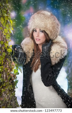pretty young woman in a winter fashion shot.Winter wild girl on snow.Winter Girl with beautiful make up, and snow flake, forest background.Portrait of attractive woman - stock photo