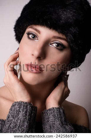 Pretty young woman in a winter fur hat looking at the camera with her hands raised to her neck, a serious expression and head tilted to the side - stock photo