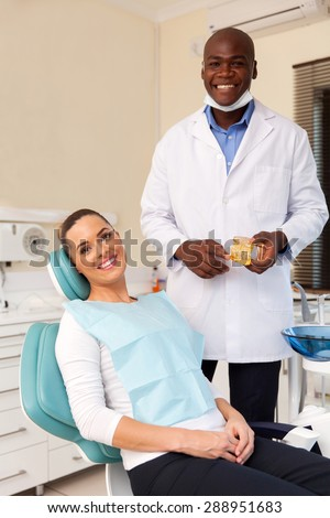 pretty young woman in dental clinic with dentist - stock photo