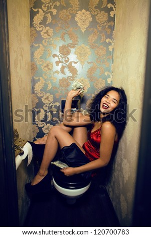 pretty young woman in restroom with money - stock photo