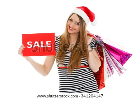 Pretty young woman in Santa's hat with shopping bags stands on a white background. Christmas sale. - stock photo