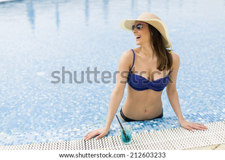 Pretty young woman in the pool - stock photo