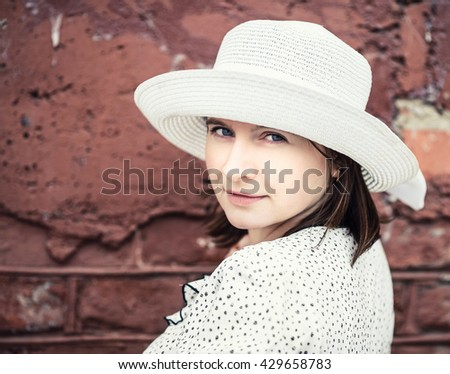 Pretty young woman in white hat against brick wall background. Close-up female portrait. Close-up vintage portrait of a woman. Vintage style photo. Shallow depth of field. Selective focus. - stock photo