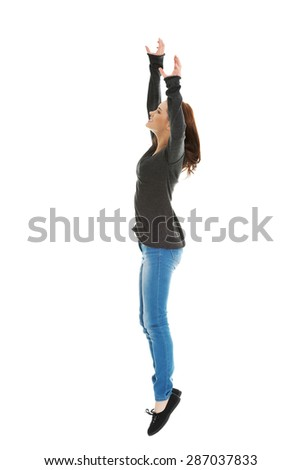 Pretty young woman jumping with hands up - stock photo