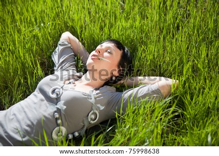 Pretty young woman lie on green grass - stock photo