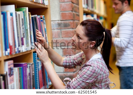 Pretty young woman looking for a book in a bookstore - stock photo