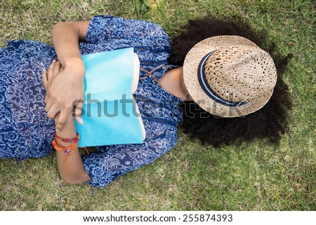 Pretty young woman napping in park on a summers day - stock photo