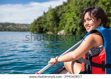 Pretty, young woman on a canoe on a lake, paddling, enjoying a lovely summer day - stock photo