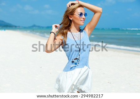 Pretty young woman outdoor closeup portrait posing on the beach blue sky nice weather on tropic island having fun in colorful dress  - stock photo