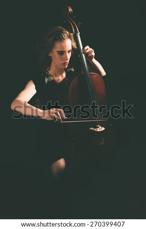 Pretty young woman playing a cello at night during a concert or classical recital sitting in her chair with the instrument in front of her - stock photo