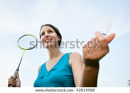 Pretty, young woman playing badminton in a city park on a lovely summer day (shallow DOF) - stock photo