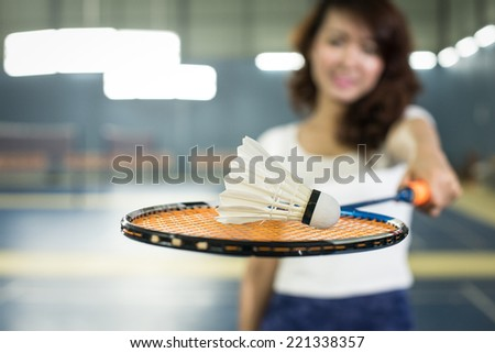 Pretty, young woman playing badminton in Gym - stock photo