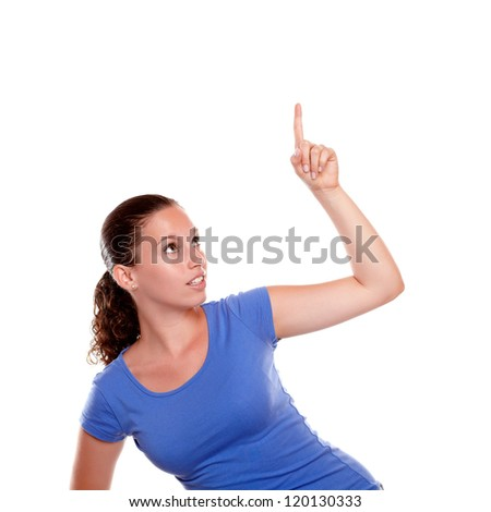 Pretty young woman pointing and looking up standing over white background - copyspace - stock photo