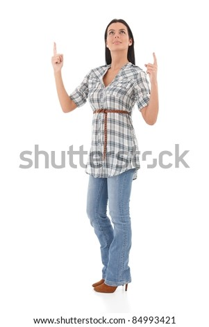 Pretty young woman pointing and looking upwards, smiling.? - stock photo