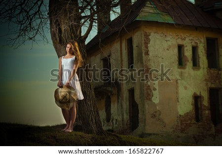 Pretty young woman posing in front of the farm. Very attractive blonde girl with white short dress holding a hat. Romantic young woman posing outdoor in the field - stock photo