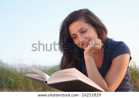 Pretty young woman reading a book outside - stock photo