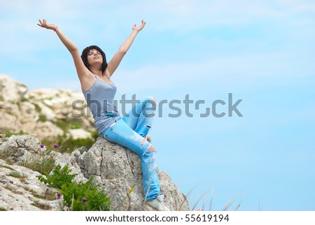 Pretty young woman relaxing on the rock - stock photo