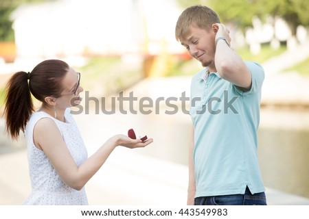 Pretty young woman requesting hand of her beloved boyfriend in park, asking to marry. Smiling girl holding box with engagement ring. Puzzled Man scratching head, thinking what to do - stock photo
