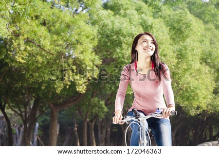 Pretty young woman riding bike in the park - stock photo
