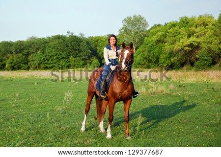 pretty young woman riding horse - stock photo