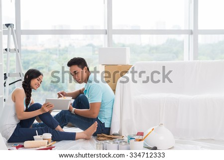 Pretty young woman showing design idea on digital tablet to her boyfriend - stock photo