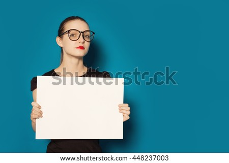 Pretty young woman showing on empty blank board. Colorful studio portrait isolated on blue background. Space for text - stock photo