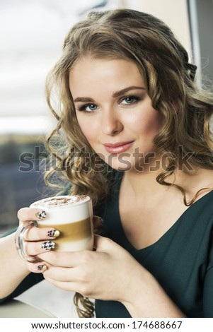 pretty young woman sitting in a cafe with a cup of coffee cappuccino - stock photo