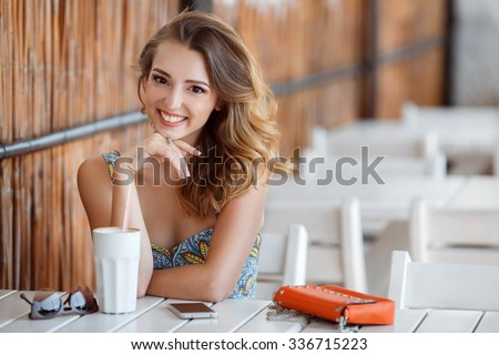 pretty young woman sitting in the cafe with a cup of tea. Charming woman in a restaurant. woman drinking coffee in the morning at restaurant (soft focus on eyes) - stock photo